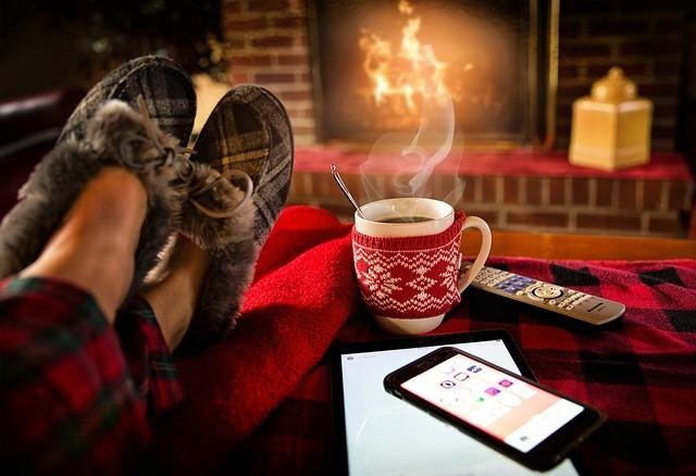 Kachlová pec s vyloženými nohami, hrnčekom a smartfónom v popredí
